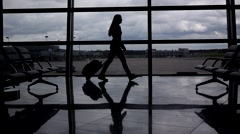 Woman silhouette stride and roll trolley case against terminal glass wall window Stock Footage