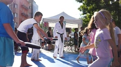 Children training karate martial arts workout session on street cultural fest Stock Footage