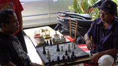 PARAPAT, INDONESIA - 21 JUNE 2016: Local people playing chess outdoor Stock Footage