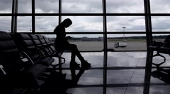 Tourist girl silhouette sit at airport against window with smartphone Stock Footage