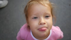 Little child girl face portrait grimace show tongue to camera slow motion Stock Footage