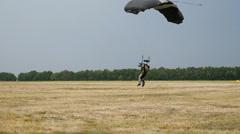 Landing parachutist on the field Stock Footage