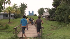 Resident of an amazonian village walk in the middle of the village. Stock Footage