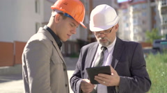 Two business partners in helmets meeting near builds and discussing. 4K Stock Footage