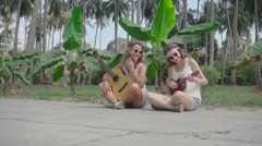 Smiling Hippie Girl Playing Guitar Sitting on the Roadside. Slow Motion Stock Footage