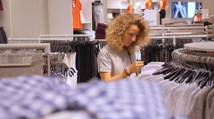 Female Buyer Choosing Clothes in Shopping Mall Stock Footage