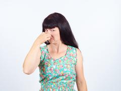 A young woman pinches the nose with fingers in disgust something stinks. Stock Photos