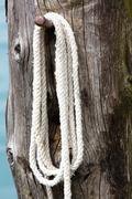 White mooring rope on wooden post Stock Photos