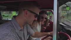 Hippie Girls Jump into the Minivan to a Young Smiling Guy. Slow Motion Stock Footage