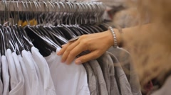 Buyer Chooses T-Shirt in Clothing Boutique with Female Clothes Stock Footage