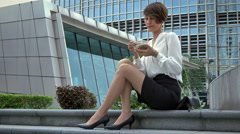 Young beautiful business woman sitting on the city street and having lunch. Stock Footage