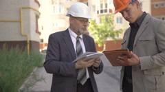 Two businessmen in helmet discussing scheme of building near builds. 4K Stock Footage