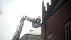 Fire brigade on lift ladder repairing the roof old building - Krakow Poland Stock Footage