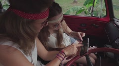 Hippie Girls Use Smartphone Sitting in a Car Cabin. Slow Motion Stock Footage
