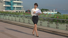 Beautiful business woman walking on the street and looking folder with documents Stock Footage