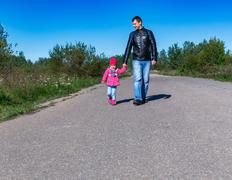 Little girl in a pink coat, jeans and boots walking the park. she goes on the Stock Photos