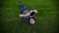Man with a hat lying on the grass in the park Stock Footage