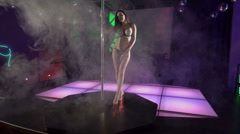 Sexy woman poledancer dancing hot pole dance on lighted stage at night club Stock Footage