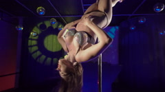 Beautiful woman performs erotic pole dance on nightclub stage floor Stock Footage