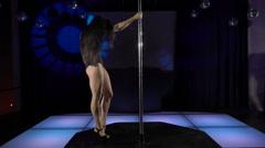 Graceful girl dancing sensual pole-dance on pole at dance night club Stock Footage