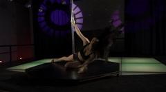 Beautiful woman dancing sensual pole dance on illuminated nightclub stage floor Stock Footage