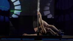 Graceful pole-dancer performs sensual pole dance on nightclub stage floor Stock Footage