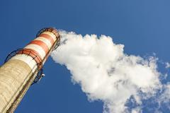 White smoke from the concrete chimney of the plant against the blue sky Stock Photos