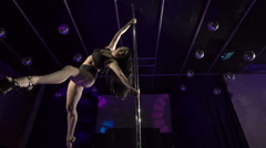 Fit woman pole dancer performs acrobatic stunts on lighted stage at nightclub Stock Footage