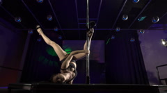 Professional performer dancing sensual pole dance on nightclub stage floor Stock Footage