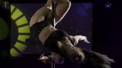 Young woman performing pole-dance tricks on pole at night club Stock Footage