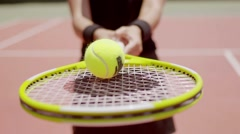 Woman tennis player balancing a ball on her racket Stock Footage