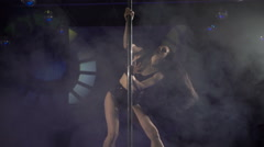 Graceful girl performing pole dance tricks on lighted stage floor in smoke Stock Footage