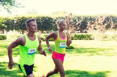 Happy sportsmen couple racing wit badge numbers Stock Photos
