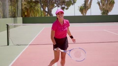 Excited young woman running across a tennis court Stock Footage