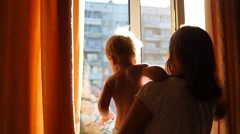 A girl with a child looking in through the window Stock Footage