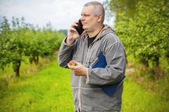 Agronomist talking on the phone in apple orchard Stock Photos