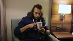 Guy sits down, takes a Cup of tea from the bedside and drink it Stock Footage
