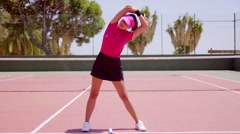 Young woman warming up before a game of tennis Stock Footage