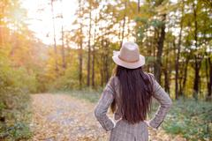 Beautiful woman in checked coat and hat, autumn forest Stock Photos