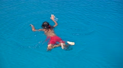 Child in red shorts snorkeling  Stock Footage