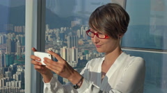 Beautiful business woman taking mobile phone selfie picture at Hong Kong skyline Stock Footage