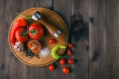 Fresh tomatoes and coarse salt for use as cooking ingredients with a halved t Stock Photos