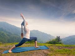 Woman doing yoga asana Virabhadrasana - Warrior pose outdoors Stock Photos