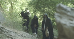 A group of monks in black clothes are moving in forest Stock Footage