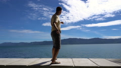 Young man plays ducks and drakes on Toba lake, Sumatra, Indonesia Stock Footage