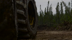 Extreme close up tractor wheels roll towards camera in forest Stock Footage