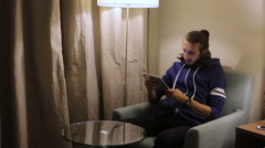 Handsome, young man with tablet computer sitting on chair at home Stock Footage