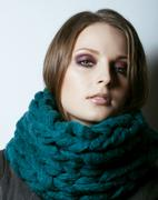 Young pretty real woman in sweater and scarf all over her face smiling Stock Photos