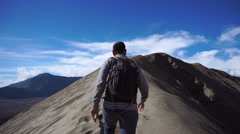 Backpacker male traveler walking at crater rim of Bromo volcano Stock Footage