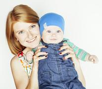 Young beauty mother with cute baby, red head happy modern family isolated on Stock Photos